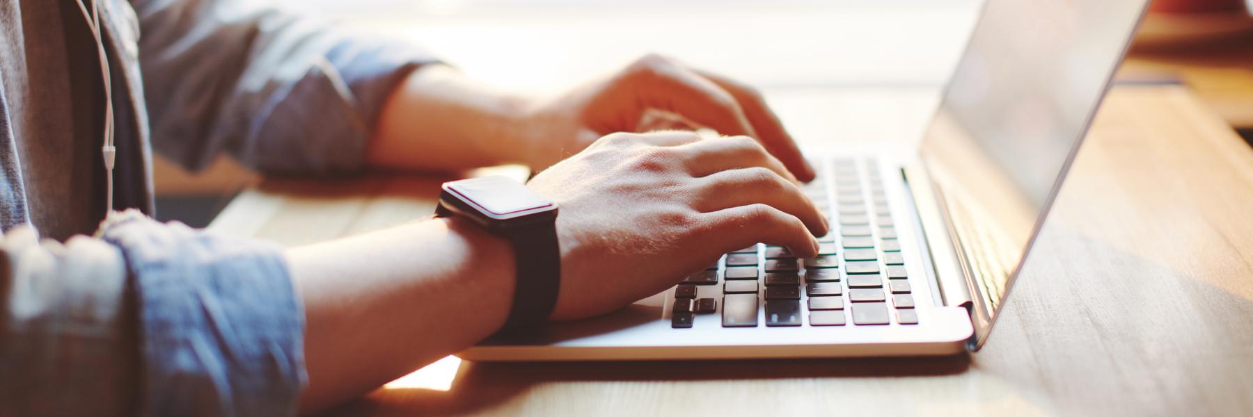 Das Bild zeigt zwei männliche Hände, die etwas am Laptop tippen.