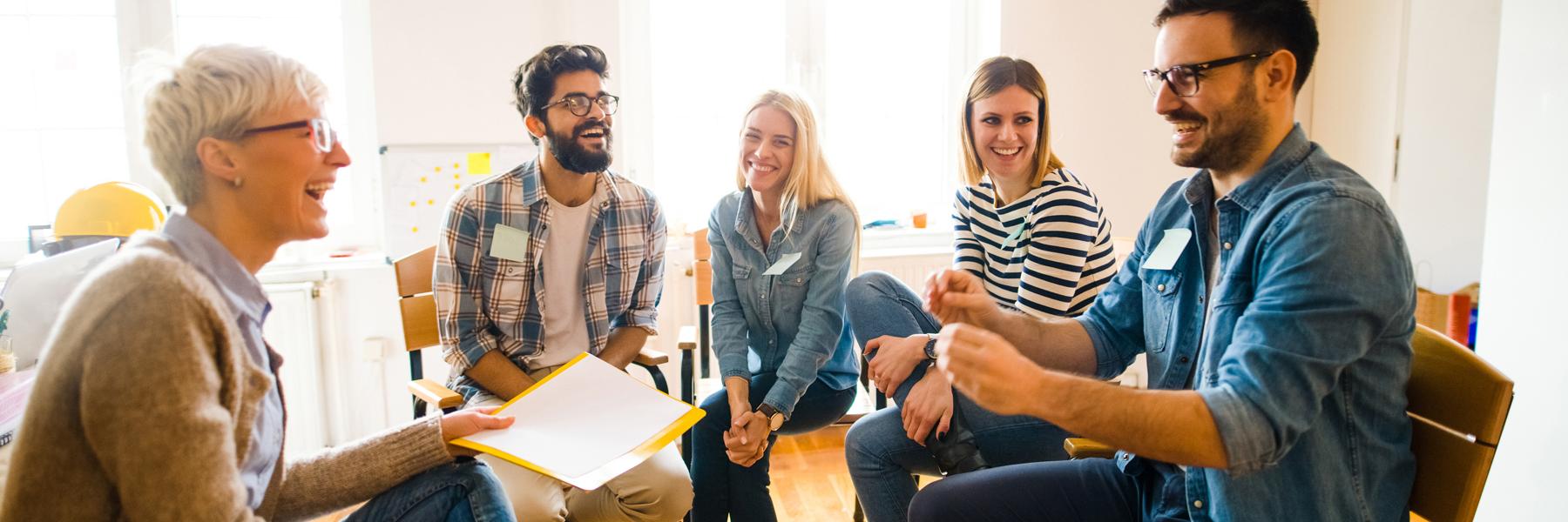 Das Bild zeigt fünf Menschen in Workshop-Atmosphäre. Sie sitzen lachend im Kreis.