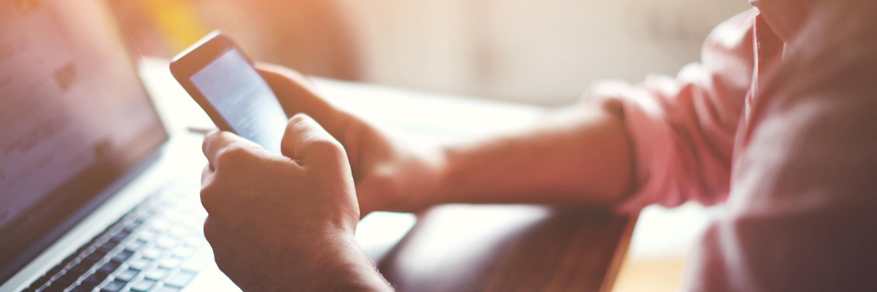 Das Bild zeigt zwei männliche Hände, die ein Smartphone bedienen.