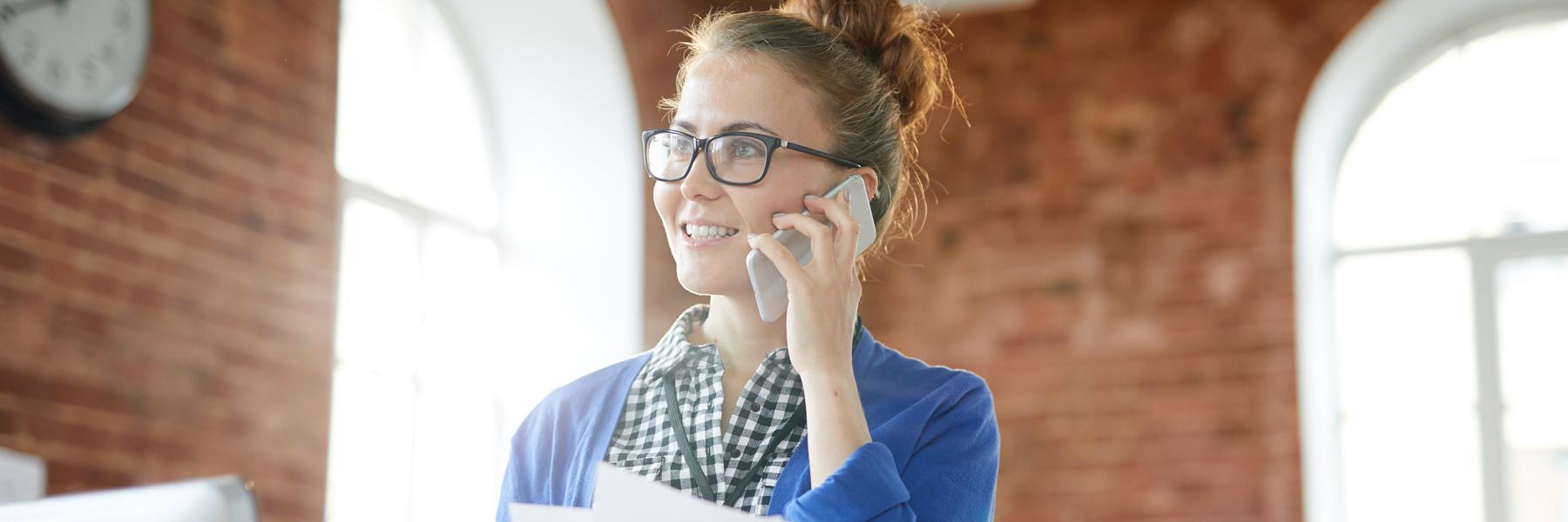 Das Bild zeigt eine junge Frau mit Brille, die mit dem Handy telefoniert.